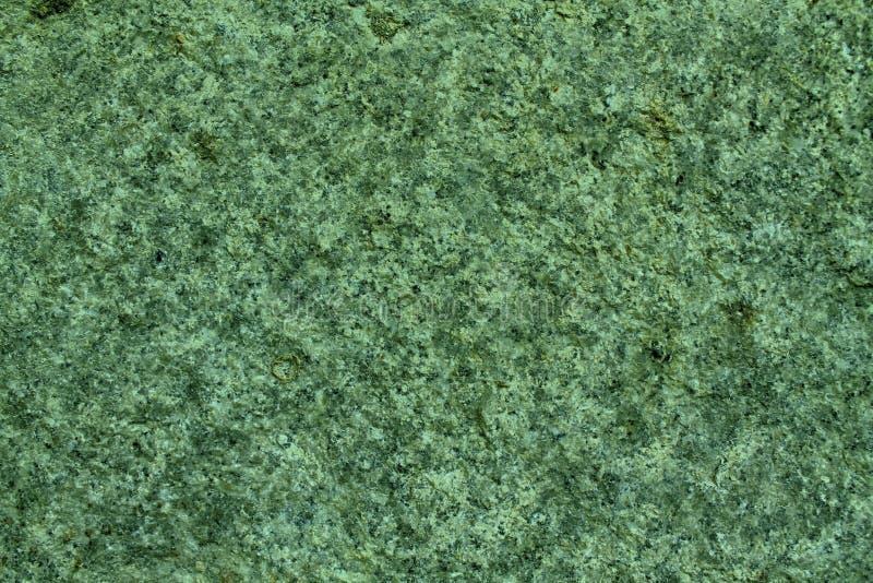 绿色花岗岩岩石特写镜头背景,石纹理,破裂的表面 免版税库存照片
