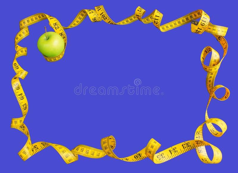 绿色苹果和测量的磁带有厘米和英寸的作为在蓝色背景隔绝的框架 图库摄影