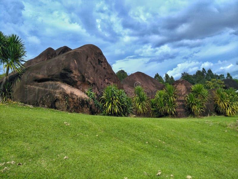 绿色草坪和大石头与阴暗天空 库存照片