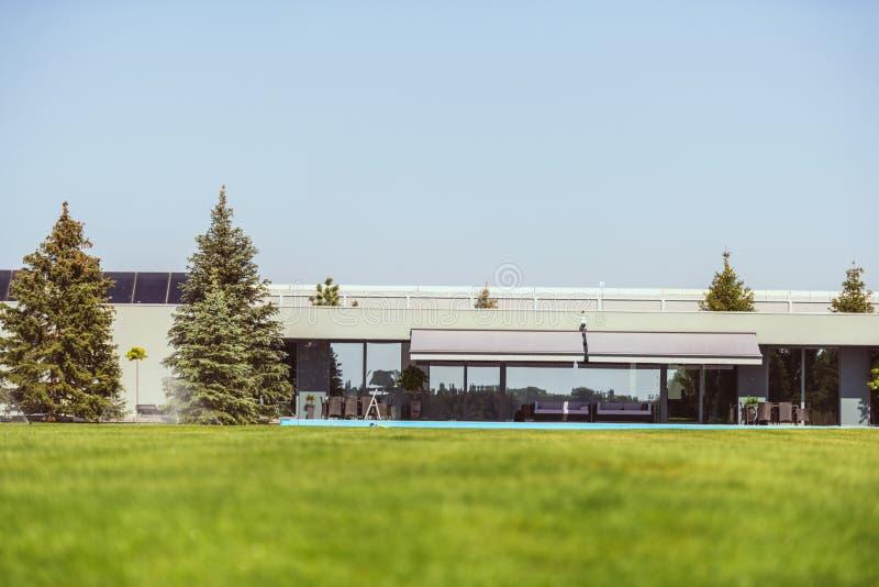 绿色草坪和现代村庄的表面水平在蓝色明白下 免版税库存图片