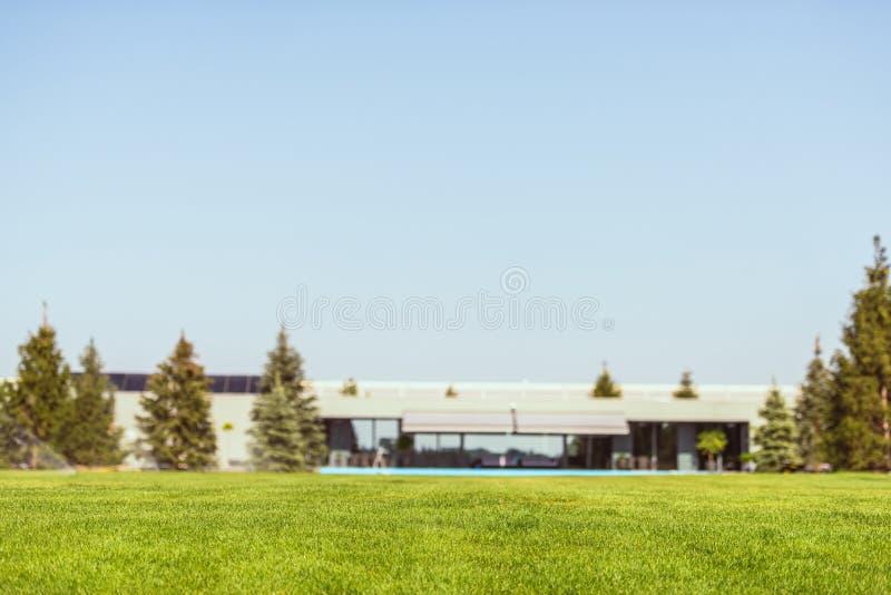 绿色草坪和现代村庄选择聚焦在蓝色明白下 免版税库存图片