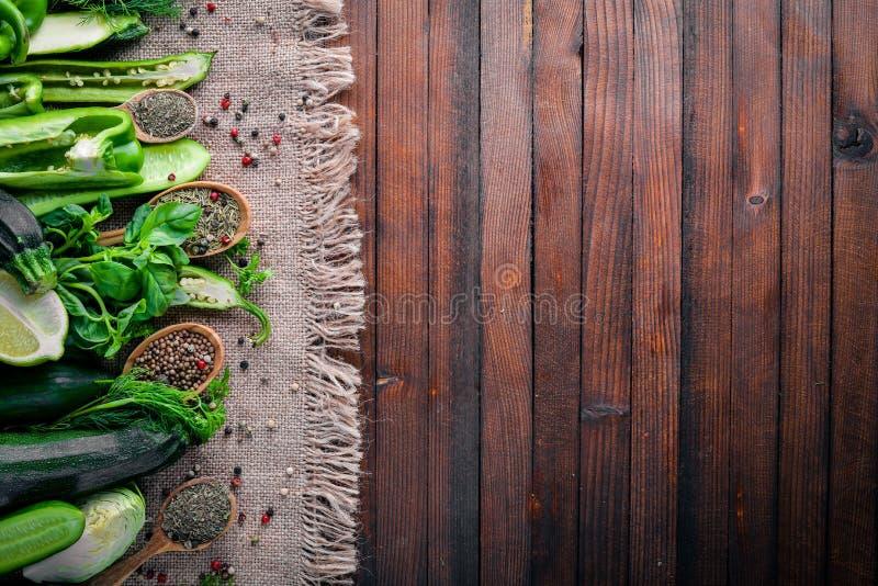 绿色菜和香料的一种大选择在木背景 免版税库存照片