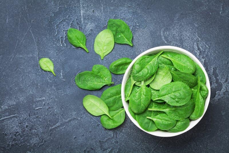 绿色菠菜在碗离开在黑台式视图 有机和饮食食物 免版税图库摄影
