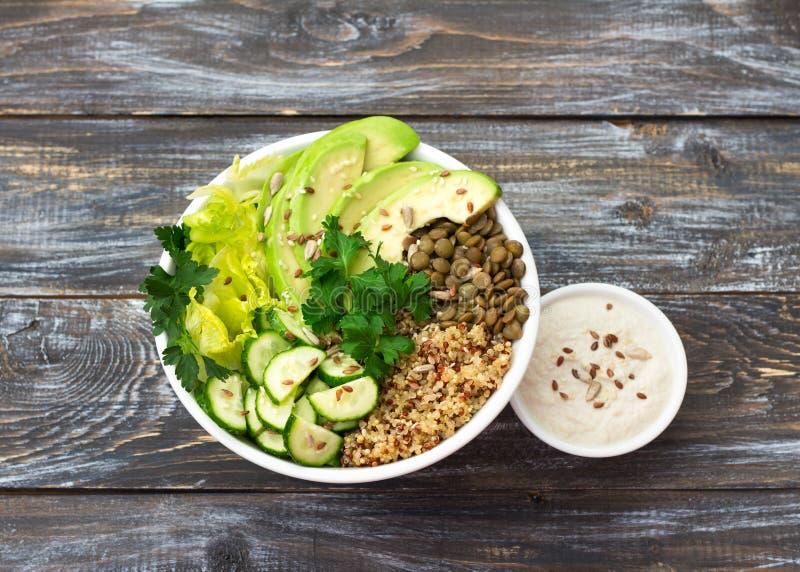 绿色菩萨碗用扁豆、奎奴亚藜、鲕梨、黄瓜、新鲜的莴苣、草本和种子 库存照片