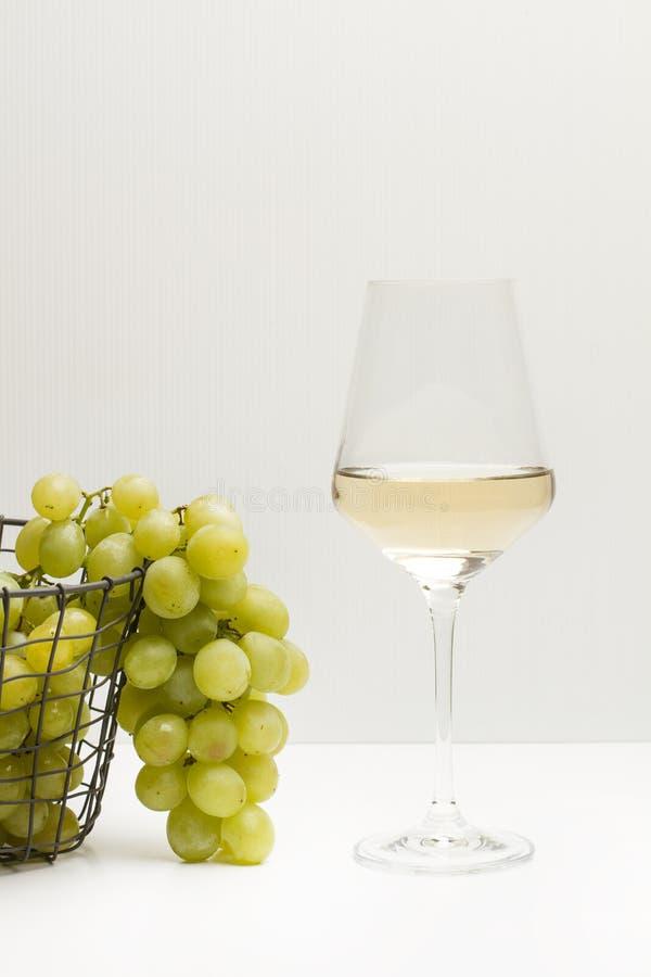 绿色葡萄和一块白葡萄酒玻璃 图库摄影