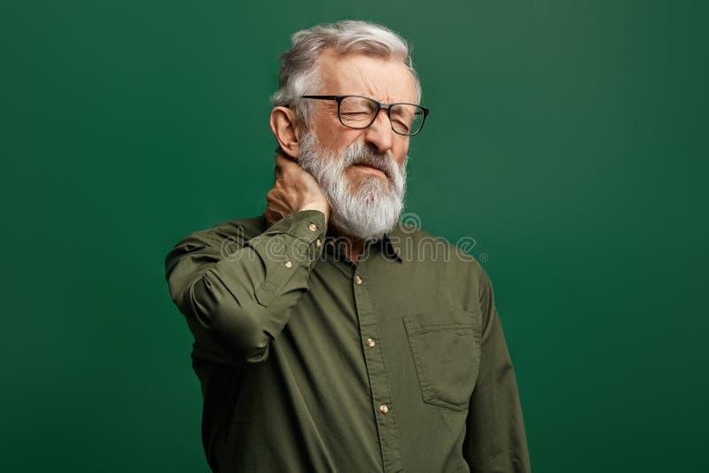 绿色衬衣的英俊的时髦的老人遭受脖子疼痛 库存照片