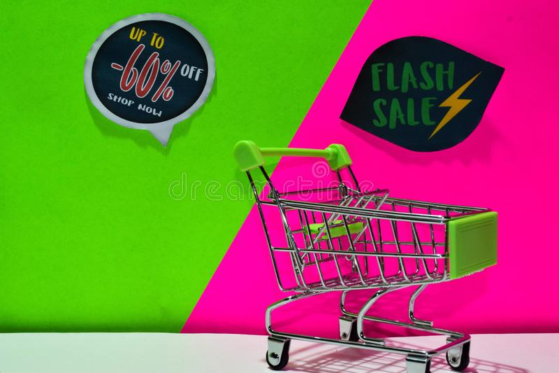 绿色购物车 附上-60%,现在购物并且闪动在绿色和桃红色背景的销售文本 库存照片