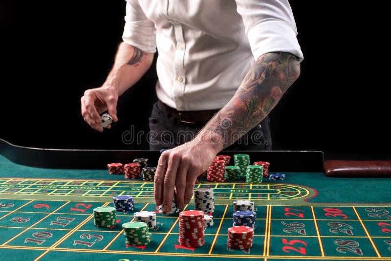 绿色赌博娱乐场桌的特写镜头充满活力的图象与轮盘赌的,用副主持人和多彩多姿的芯片的手 免版税库存图片