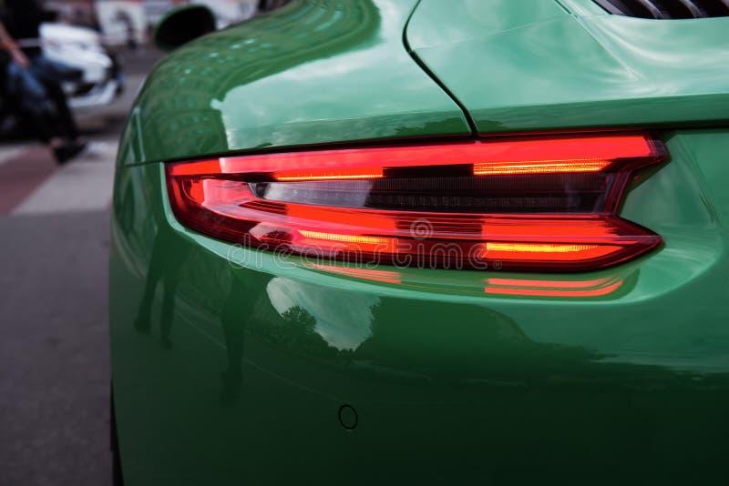 绿色跑车 汽车背后照明在行人穿越道前 库存照片