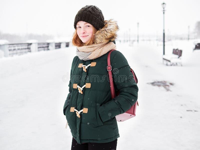绿色附头巾皮外衣帽子的可爱的愉快的年轻红头发人妇女获得乐趣在多雪的冬天探索的河码头 库存照片