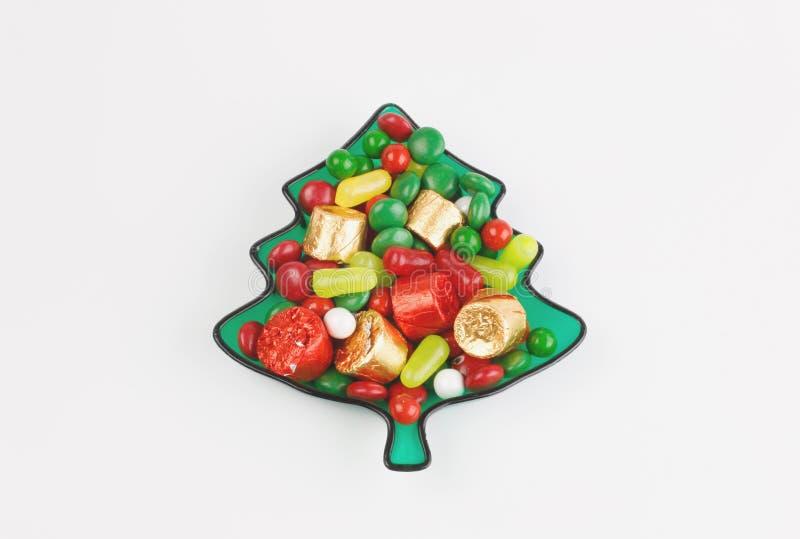 绿色陶瓷一棵圣诞树用在白色背景中隔绝的糖果 免版税库存图片