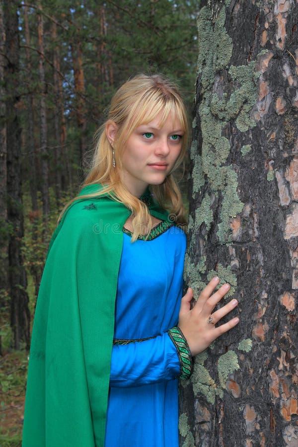 绿色雨衣的女孩,紧贴在杉木 免版税图库摄影