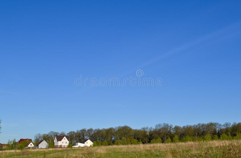 绿色领域的小家庭房子与蓝天 免版税库存照片