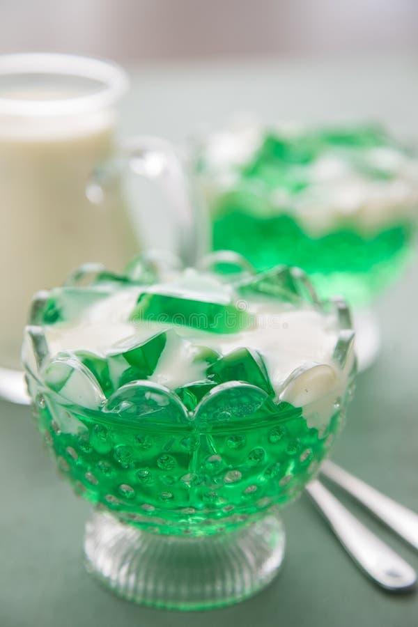 绿色香车叶草Jell-O和在玻璃碗的香草调味汁 免版税库存图片