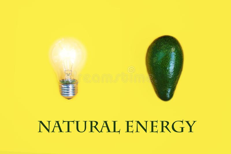 绿色鲕梨作为重要能量的来源在电灯泡关闭旁边的,在黄色背景 明亮的医疗保健 免版税库存图片