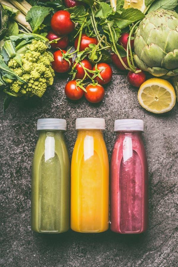 绿色,红色和黄色五颜六色的有机蔬菜、水果和莓果圆滑的人与成份在瓶在灰色花岗岩桌上 库存图片