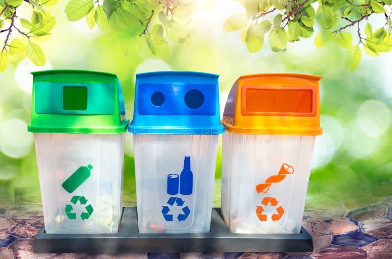绿色,黄色,蓝色和在自然bokeh背景与回收标志隔绝的回收站 免版税库存照片