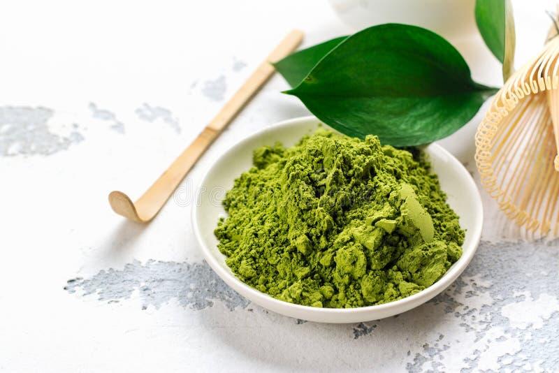 绿色matcha茶粉末和茶辅助部件在白色背景 免版税库存图片