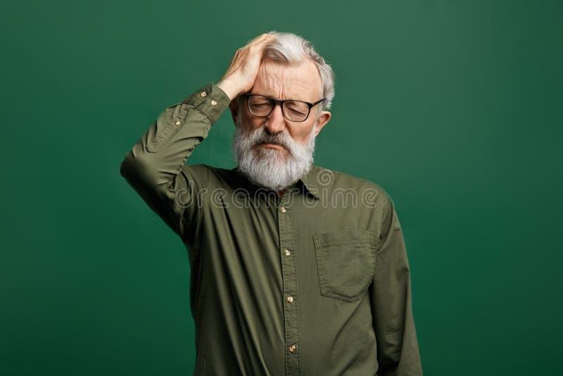 绿色T恤杉痛苦的可爱的老人从头疼,颅内的压力 免版税图库摄影