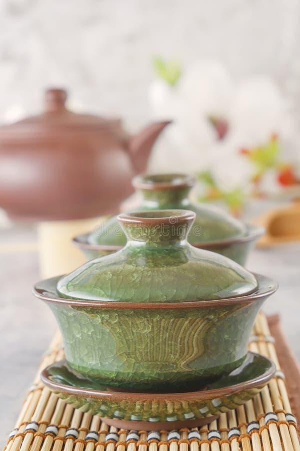 绿茶和属性茶道的-安置一个陶瓷茶壶、杯子、过滤器、筷子和镊子 库存照片