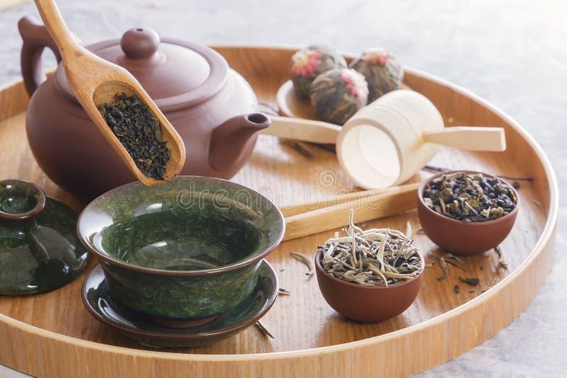 绿茶和茶道属性-陶瓷茶壶、杯子、过滤器、筷子和镊子 免版税库存照片