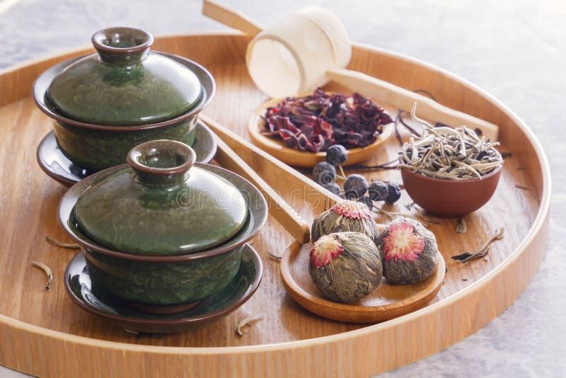 绿茶和茶道属性-陶瓷茶壶、杯子、过滤器、被安置的筷子和镊子 免版税图库摄影