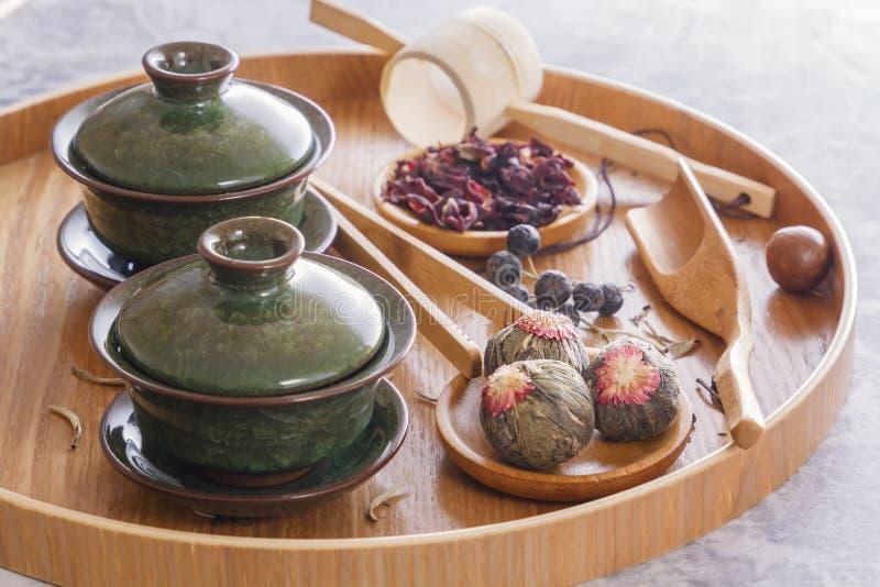 绿茶和茶道属性-陶瓷茶壶、杯子、过滤器、被安置的筷子和镊子 免版税库存照片