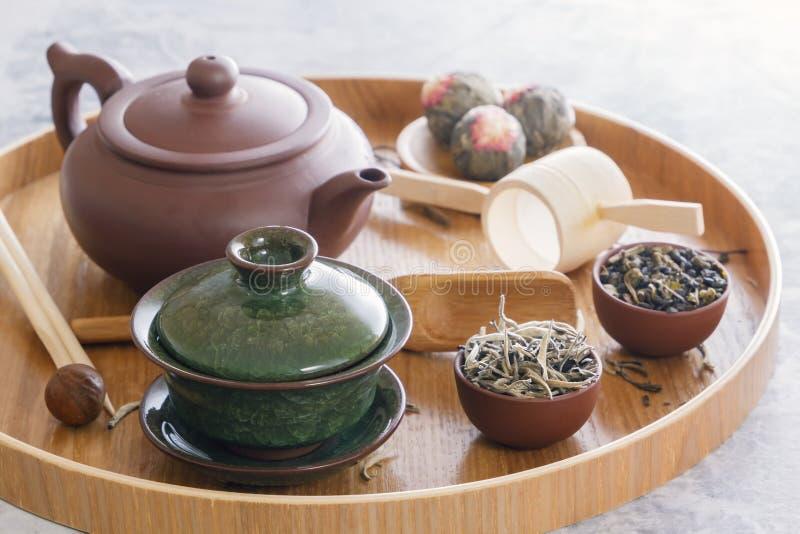 绿茶和茶道属性-陶瓷茶壶、杯子、过滤器、被安置的筷子和镊子 图库摄影