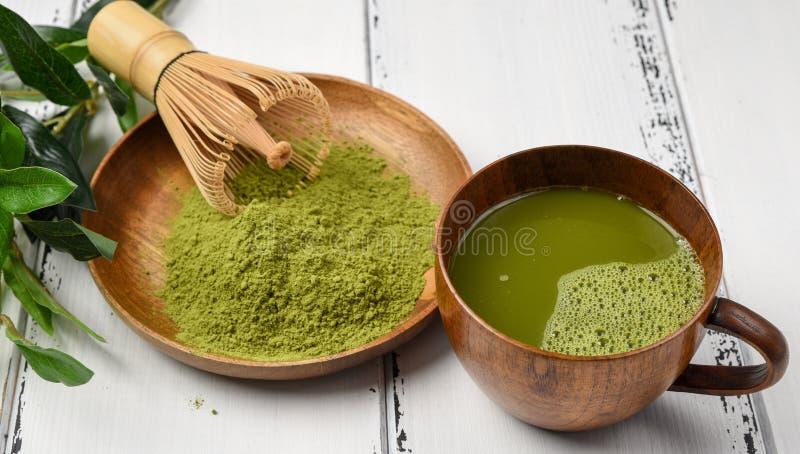 绿茶在一个木碗的matcha粉末有扫和木匙子的 免版税库存照片
