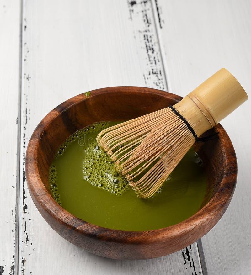 绿茶在一个木碗的matcha粉末有扫和木匙子的 库存照片