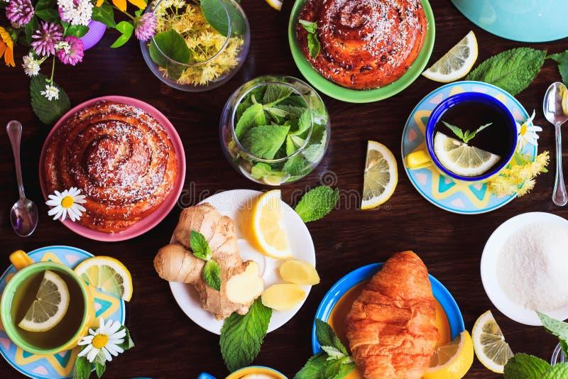 绿茶用柠檬和薄菏和与一个酥脆外壳的不同的焙烤食品在木背景 图库摄影