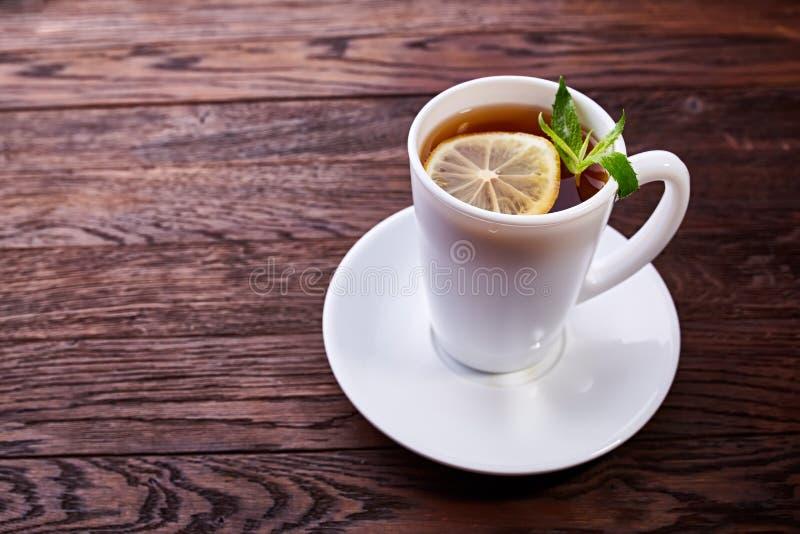 绿茶用柠檬和薄菏在木桌背景 免版税库存图片