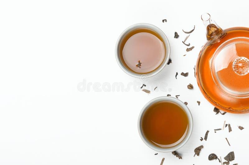 绿茶酿造了在一个透明茶壶和在一张白色桌上的小杯子用疏散茶 概念茶道 免版税库存照片