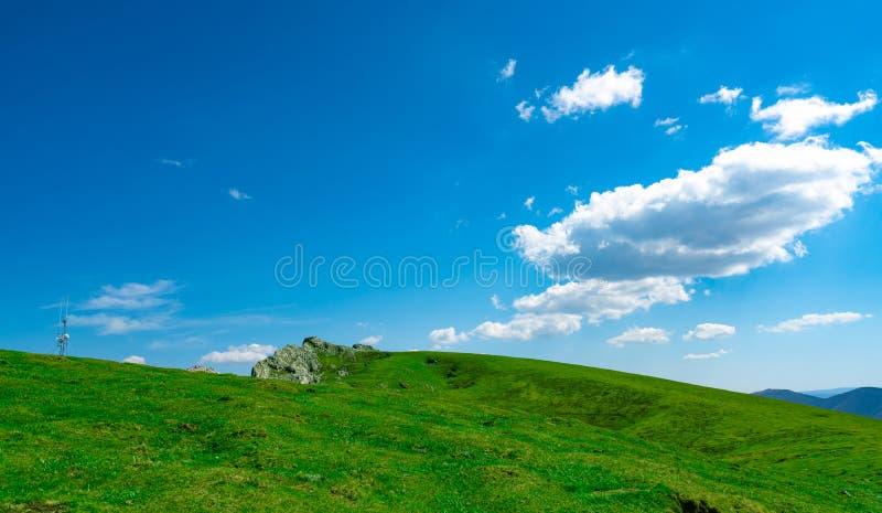 绿草和岩石小山风景在春天有美丽的天空蔚蓝和白色云彩的 乡下或农村看法 ?? 库存照片