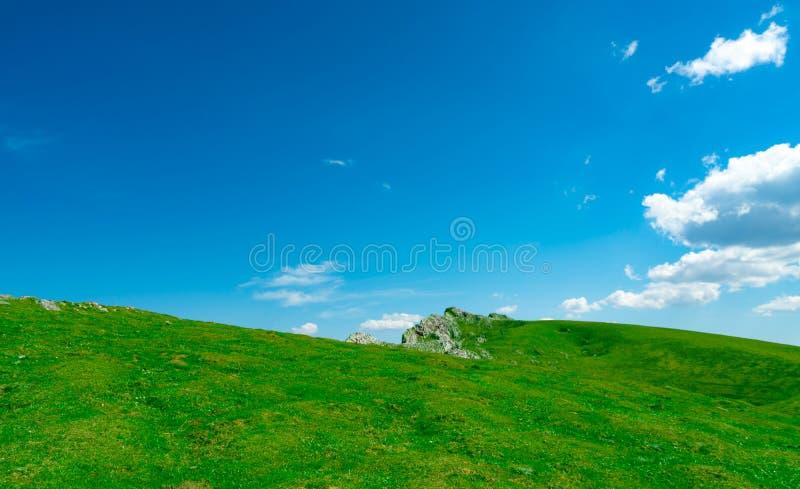 绿草和岩石小山风景在春天有美丽的天空蔚蓝和白色云彩的 乡下或农村看法 ?? 图库摄影