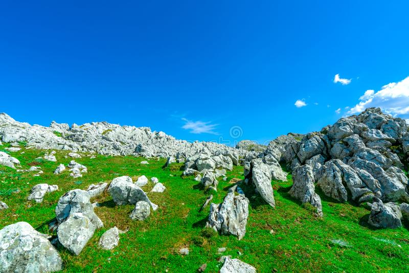 绿草和岩石山风景在春天有美丽的天空蔚蓝和白色云彩的 乡下或农村看法 ?? 免版税库存照片