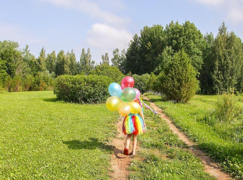 绿草的可爱的女孩与五颜六色的明亮的气球 库存照片
