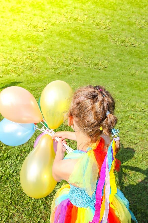 绿草的可爱的女孩与五颜六色的明亮的气球 库存图片