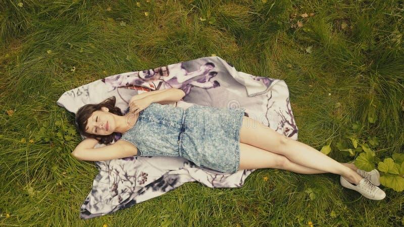 绿草的天空视图快乐的少妇 放松在草的美丽的女孩 免版税库存照片