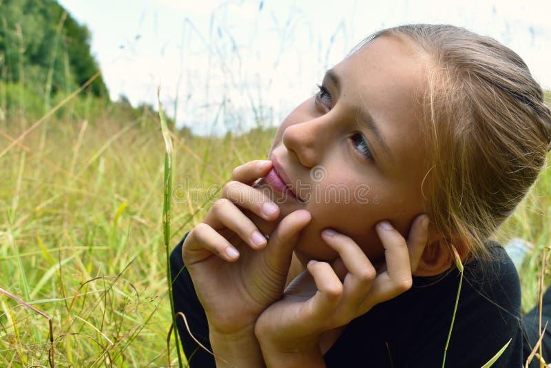 绿草的美丽的女孩在夏天 免版税库存照片