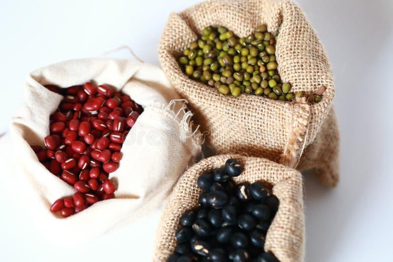 绿豆ï ¼ ŒRed大豆豆和黑大豆豆在布料传送带 库存图片