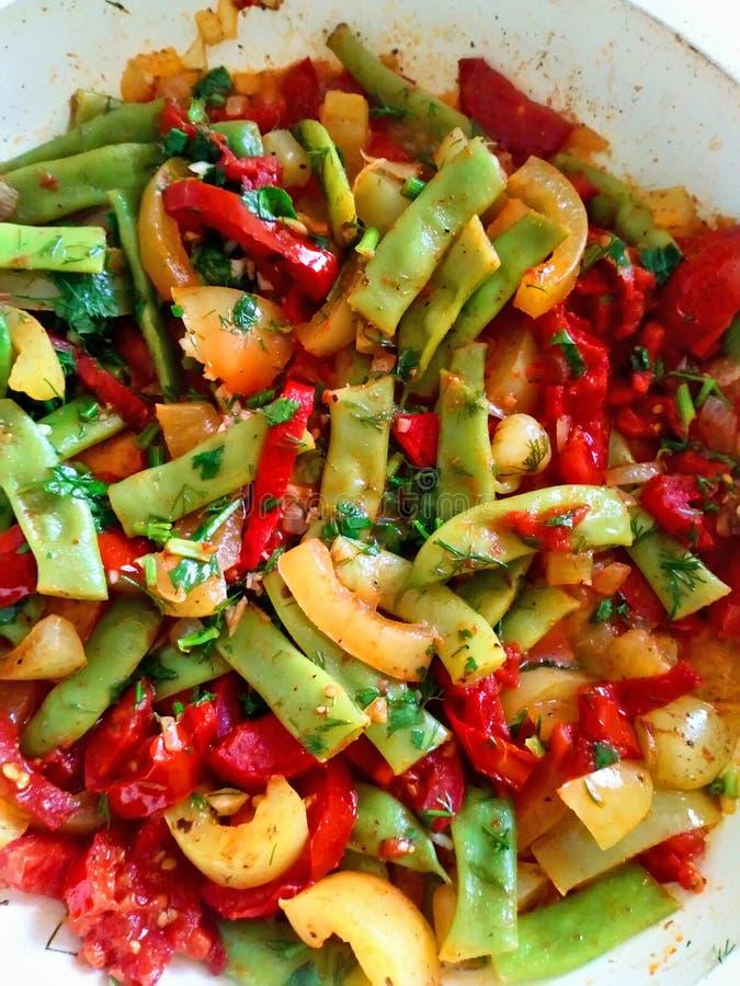 绿豆用烹调在平底锅的蕃茄和甜椒 免版税库存照片