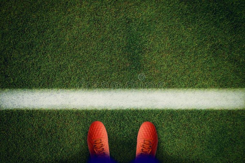 绿野上红色足球靴的顶视图 免版税图库摄影