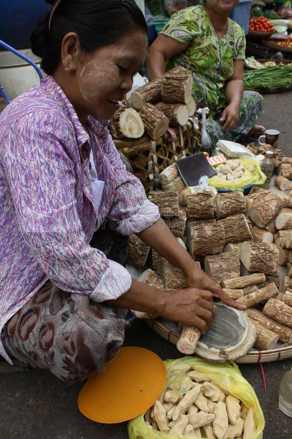缅甸夫人在一个市场上的做Thanaka在仰光 免版税库存照片