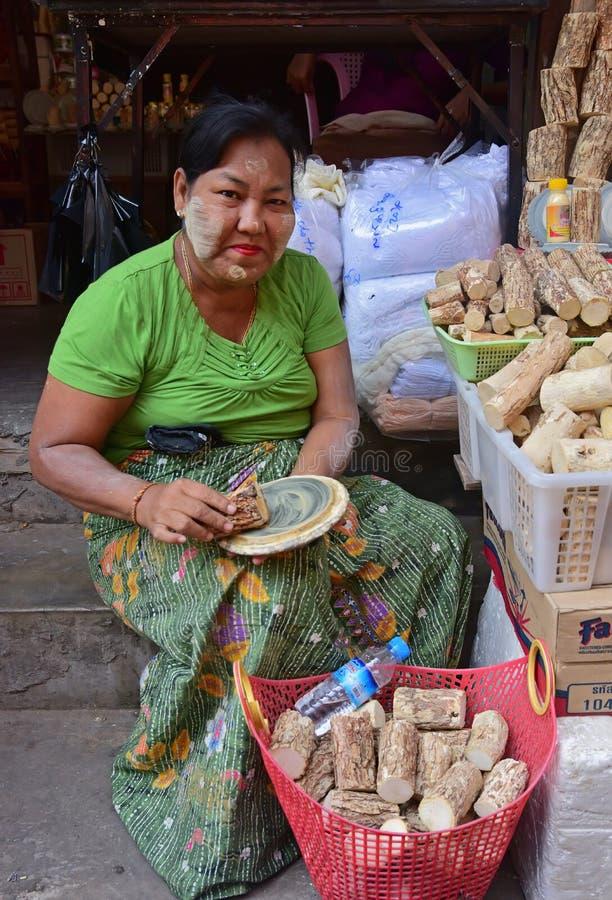 缅甸老妇人展示如何制作新的檀娜卡化妆品膏