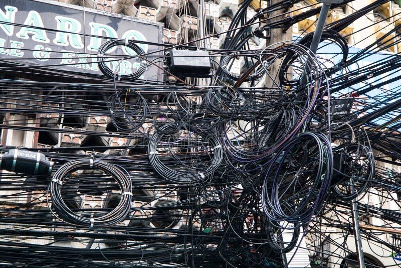 缆绳和导线混乱在一根电杆 许多电缆-导线和电话 免版税库存照片