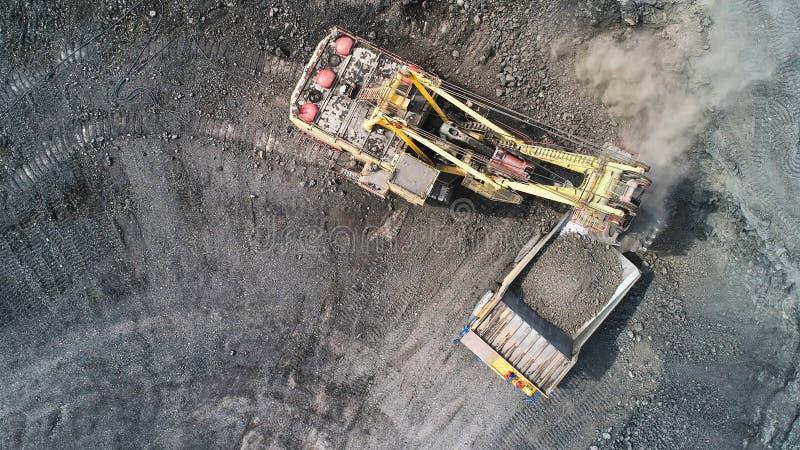 缆绳挖掘机装载从一个矿用汽车的身体装载过多 免版税图库摄影