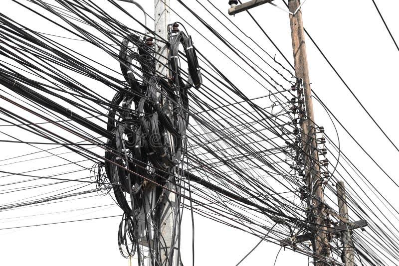 缆绳杂乱混乱与导线的在白色的电杆 库存照片
