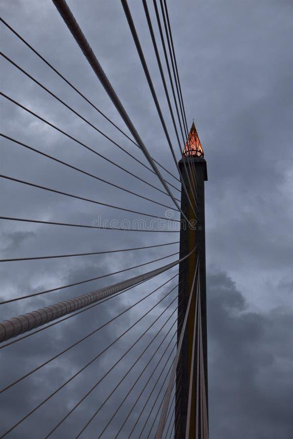 缆绳被停留的桥梁定向塔上面的火炬形式在黄昏的 图库摄影