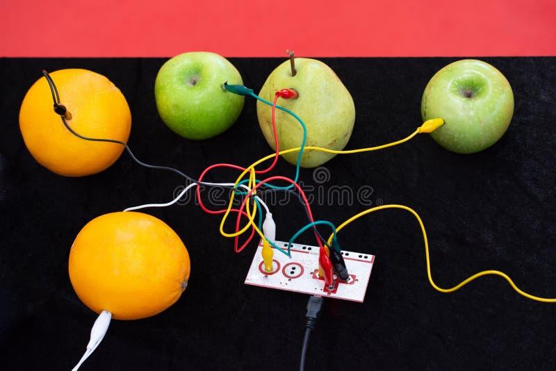 缆绳被连接到设备和到苹果、桔子和梨 库存图片